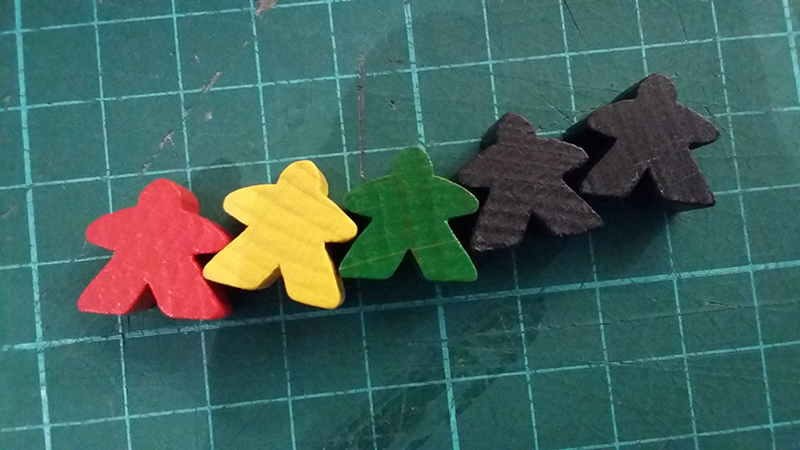 Image showing Carcassonne's meeples. It looks like I'm about to dissect them on my cutting mat, but I assure you no meeples were harmed in the writing of this article.